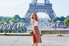 Beautiful young Parisian woman near the Eiffel tower Stock Images