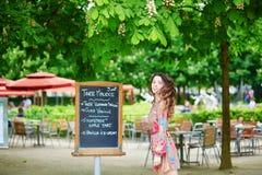 Beautiful young Parisian woman reading menu Stock Photography