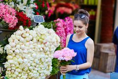 Beautiful young Parisian woman selecting peonies Stock Photo