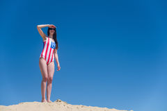 Beautiful young patriot USA on blue sky background in a swimsuit Royalty Free Stock Images