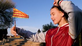 Beautiful young patriotic teen make selfie with Barcelone flag on the background. Amazing Barcelone, Spain. Beautiful young teen make selfie with Barcelone flag stock footage