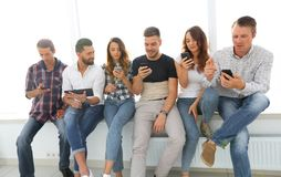 Young people in casual clothes using gadgets. Beautiful young people in casual clothes using gadgets while sitting together on the window sill Royalty Free Stock Images