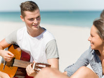 Beautiful young people with guitar on beach Royalty Free Stock Photography