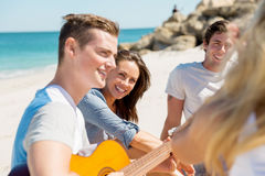 Beautiful young people with guitar on beach Royalty Free Stock Photo