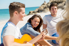 Beautiful young people with guitar on beach Stock Photography