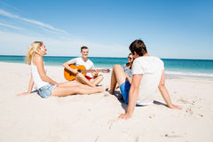 Beautiful young people with guitar on beach Royalty Free Stock Images