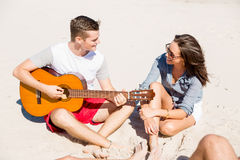 Beautiful young people with guitar on beach Stock Photos