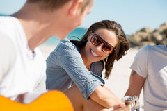 Beautiful young people with guitar on beach Stock Photo