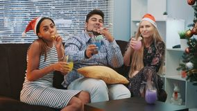 Beautiful young people in Santa hats making cheers and blowing party whistle. They sittng on sofa, smiling and drinking. Friends happiness concept stock footage