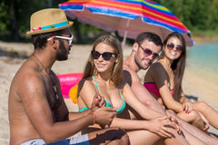 Beautiful young people are sunbathing on the beach. Royalty Free Stock Images