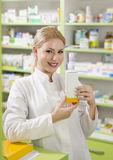 Beautiful young pharmacist girl holding medicine box Royalty Free Stock Photography
