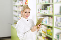 Beautiful young pharmacist with tablet Royalty Free Stock Image