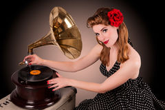 Beautiful young pin-up listens to retro gramophone Royalty Free Stock Photo