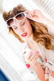 Beautiful young pinup girl having fun reading message on mobile cell phone and wearing sunglasses closeup portrait picture Royalty Free Stock Photography