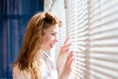 Beautiful young pinup girl looking or spying through white sun lighted window blinds portrait picture. Elegant pretty woman looking through white window blinds Stock Images