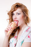 Beautiful young pinup woman eating ice cream cone looking in camera isolated on white copyspace background portrait image stock image