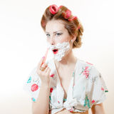 Beautiful young pinup woman shaving face with foam and razor Royalty Free Stock Photos