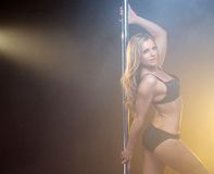 Beautiful young pole dancer with blond hair Royalty Free Stock Image