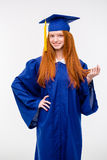 Beautiful young positive woman in graduation cap and gown Royalty Free Stock Image