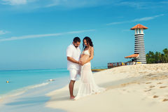 Beautiful young pregnant couple on the Caribbean coast. Royalty Free Stock Photo