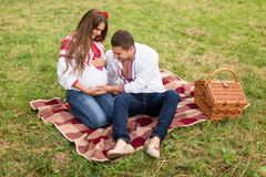 Beautiful young pregnant couple dressed in national ukrainian style having picnic in autumn park. Maternity and family happyness c Stock Photography