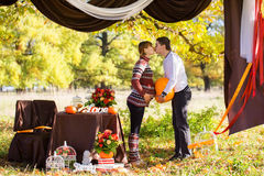Beautiful Young Pregnant Couple Having Picnic in autumn Park. Ha Stock Images