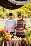 Beautiful Young Pregnant Couple Having Picnic in autumn Park. Ha Royalty Free Stock Photography