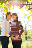 Beautiful Young Pregnant Couple Having Picnic in autumn Park. Ha Royalty Free Stock Images