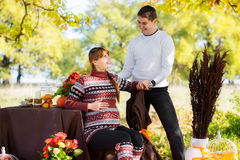 Beautiful Young Pregnant Couple Having Picnic in autumn Park. Ha Royalty Free Stock Image