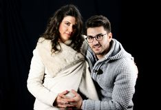 Beautiful young pregnant couple in winter clothes embraced Stock Photo