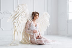 Beautiful young pregnant girl with big angel wings Royalty Free Stock Images