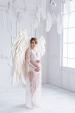 Beautiful young pregnant girl with big angel wings. In white studio Royalty Free Stock Photos