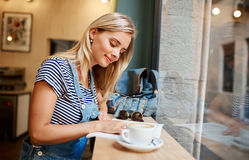 Beautiful young pregnant girl sitting in cafe reading magazine a Stock Photo