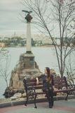 Beautiful young pregnant lady woman with brunette hair lonely dreaming sitting on wooden beanch in waterfront autumn city with ama. Zing monument on background Royalty Free Stock Images