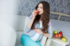 Beautiful young pregnant woman with apples. Royalty Free Stock Photo