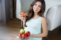 Beautiful young pregnant woman with apples. Royalty Free Stock Images
