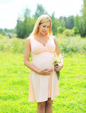 Beautiful young pregnant woman with chamomiles flowers in sunny summer Royalty Free Stock Image
