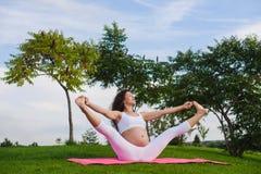 Pregnant woman doing yoga outdoors. Beautiful young pregnant woman doing yoga in park. Urdhva upavistha konasana. Sky and trees in background Stock Photography