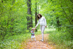 Beautiful young pregnant woman and her baby daughter Royalty Free Stock Photo