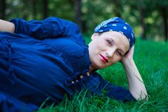 Beautiful young pregnant woman in nature couched. Green-eyed beautiful young pregnant woman dressed in blue and with a bandanna in nature couched Royalty Free Stock Photos