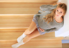 Beautiful young pregnant woman sits on the steps of a wooden ladder.  Royalty Free Stock Photo