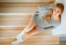 Beautiful young pregnant woman sits on the steps of a wooden ladder.  Royalty Free Stock Image