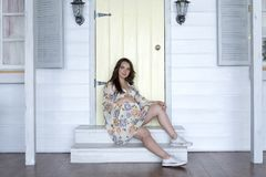 Beautiful young pregnant woman sits on the steps of a wooden ladder. Beautiful young pregnant woman sitting on the steps of wooden stairs on the porch of the Stock Images