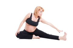 Beautiful young pregnant woman stretching on the floor Stock Image