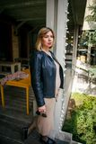 Beautiful young pregnant woman wearing dress and leather shirt resting in city park cafe stock image