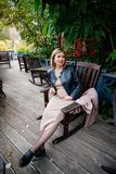 Beautiful young pregnant woman wearing dress and leather shirt resting in city park cafe, stylish pregnancy shot. Beautiful woman royalty free stock images