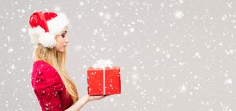 Beautiful, young and pretty girl in Christmas hat over background with snow. royalty free stock images
