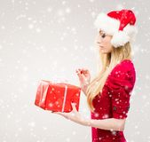 Beautiful, young and pretty girl in Christmas hat over background with snow. stock photography