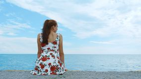 A beautiful young pretty girl is sitting on the pier of the seaport. stock video