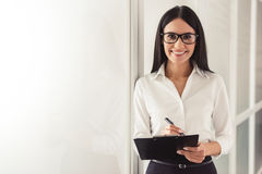 Beautiful young psychotherapist. Is making notes, looking at camera and smiling while standing in office Royalty Free Stock Images